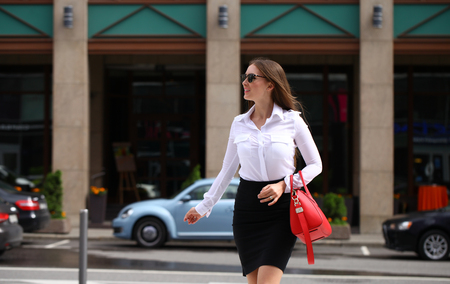 woman white shirt: Young beautiful brunette woman with a bag in his hand