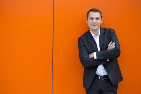 traje formal: Close up retrato de un hombre de negocios joven en un traje oscuro y camisa blanca, contra el telón de fondo de una pared de color naranja Foto de archivo
