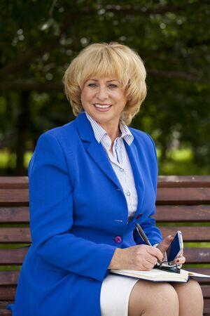 beautiful middle aged woman: Close up portrait of a beautiful middle aged woman in a blue business suit