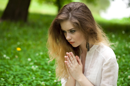 orison: Young beautiful girl praying sitting on the green lawn in the summer park