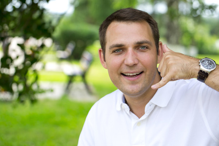 30 years old man: Attractive 30 years old caucasion man making a call me gesture, outdoors summer park