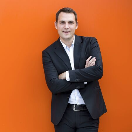 englishman: Close up portrait of a young business man in a dark suit and white shirt, against the backdrop of an orange wall Stock Photo