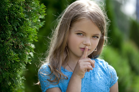 quiet baby: Young beautiful Little girl  has put forefinger to lips as sign of silence Stock Photo