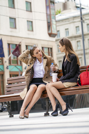 drinks after work: Two young girlfriends sitting on a bench in the town center