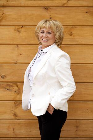 pared madera: Mujer mayor feliz en una chaqueta blanca en el fondo de la pared de madera Foto de archivo