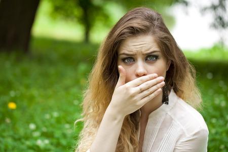 boca cerrada: Muchacha hermosa joven que cubre su boca con la mano, posando al aire libre en el parque de verano