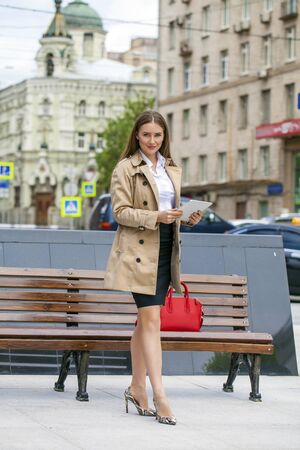 decides: Business woman in a beige raincoat holding a tablet in the summer city