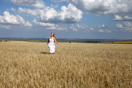 vestido blanco: Full length portrait of a beautiful young happy woman in a white dress running through the wheat field