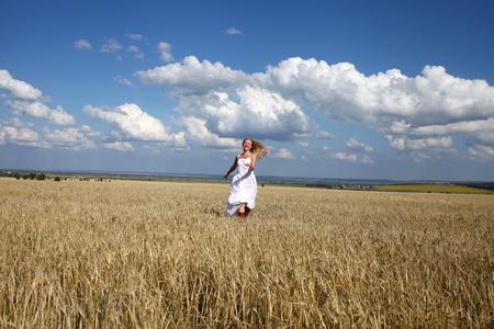 vestido blanco: Retrato de cuerpo entero de una mujer joven feliz con un vestido blanco que atraviesa el campo de trigo Foto de archivo