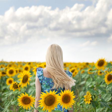 Close-up portret van een mooi jong meisje in blauwe jurk op een achtergrond gebied van de zonnebloemen
