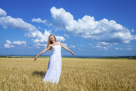 vestido blanco: Retrato de cuerpo entero de la joven y bella mujer en un vestido largo blanco est� de pie en un campo de trigo