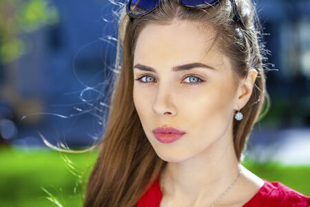 red shirt: Close up portrait of a beautiful young girl in red shirt on the background of the urban landscape