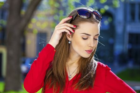 calm woman: Close up portrait of a beautiful young girl in red shirt on the background of the urban landscape