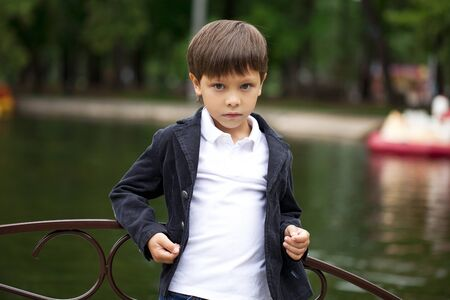 Portrait of adorable and fashionable little boy outdoor at the nice summer day Stock Photo