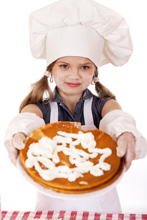 seven year old: Beautiful happy seven year old girl in chef uniform with shortcakes and whipped cream, studio on white background
