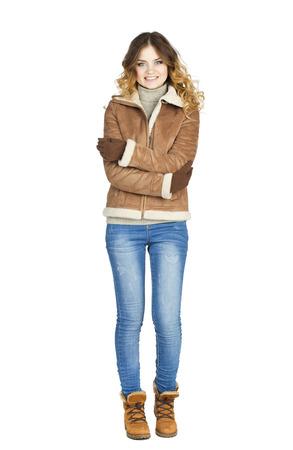 de vaqueros: Muchacha hermosa joven en un abrigo de piel de oveja de cuero y pantalones vaqueros azules aislados sobre fondo blanco Foto de archivo