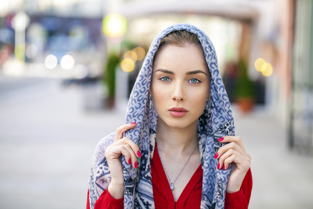 Beautiful young brunette woman in a blue scarf on summer street city