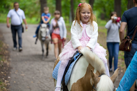 pony girl: Happy Little girl riding on a pony in a city park