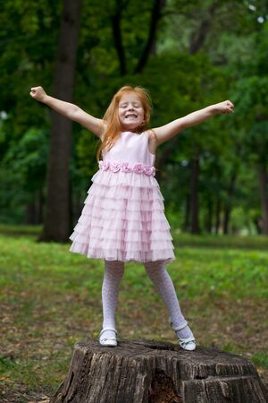 dutch girl: Portrait of a little red-haired girl on the background of summer green forest