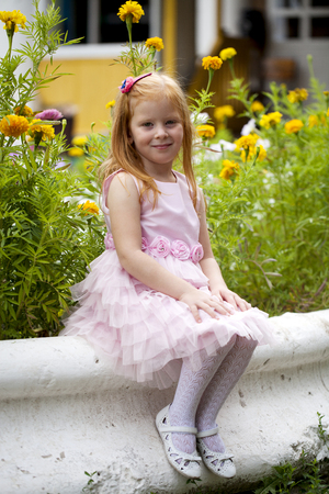 dutch girl: Portrait of a little red-haired girl on the background of a flower bed