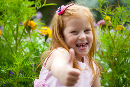 Portrait of a little red-haired girl on the background of a flower bed