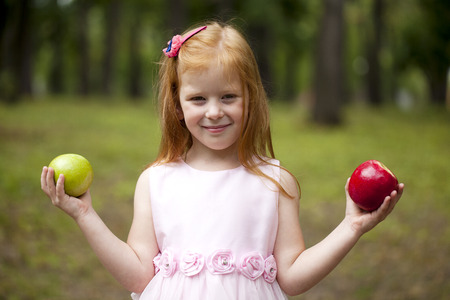 dutch girl: Happy little red-haired girl in a pink dress holding two apples, summer green park Stock Photo
