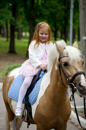 dutch girl: Happy Little girl riding on a pony in a city park
