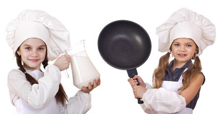 dripping pan: Cooking and people concept - Two Little girls in a white apron holding a jug of milk and dripping pan, isolated on white