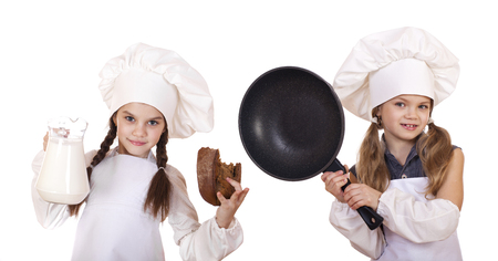 dripping pan: Cooking and people concept - Two Little girls in a white apron holding a jug of milk and dripping pan, isolated on white background