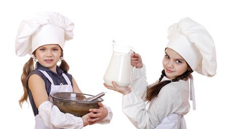 ni�as peque�as: Cocina y concepto de la gente - Dos ni�as en un delantal blanco que sostiene una jarra de leche y taz�n, aislado en fondo blanco