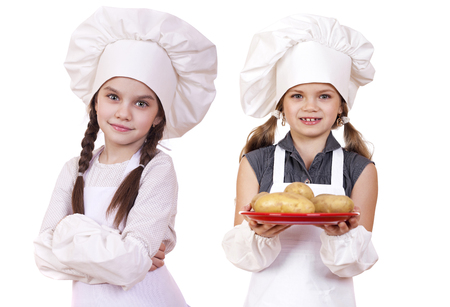 little girls: Cooking and people concept - Two Little girls in a white apron, isolated on white  Фото со стока