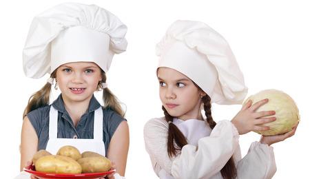 ni�as peque�as: Cocina y concepto de la gente - Dos ni�as peque�as en un delantal blanco, aislado en blanco Foto de archivo