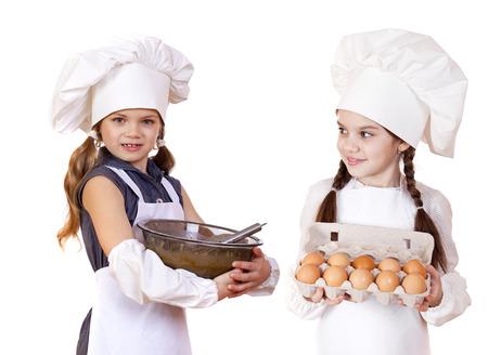 ni�as peque�as: Dos ni�as en un delantal de la celebraci�n de la caja blanca de huevos crudos y plato, aislados en blanco