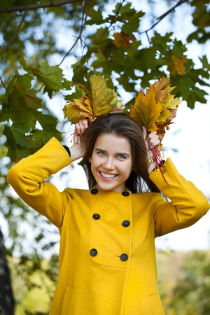 autumn young: Beautiful young woman in yellow coat in autumn park