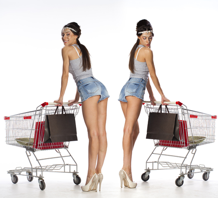 sexy young girls: Collage, Smiling brunette women posing next to an empty shopping cart isolated on white background Фото со стока