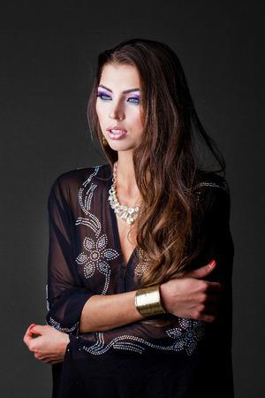black girl nude: Beautiful young woman in black tunic Arabic, on gray background