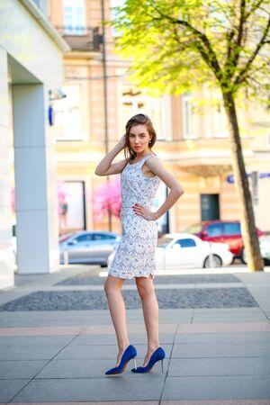 vestido blanco: Joven y bella mujer en vestido blanco calle peatonal verano Foto de archivo