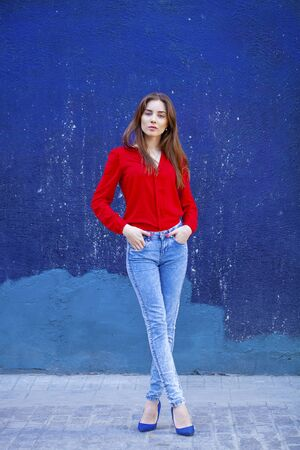 girl in full growth: Portrait in full growth the young beautiful girl in blue jeans and a red shirt on the background of color wall