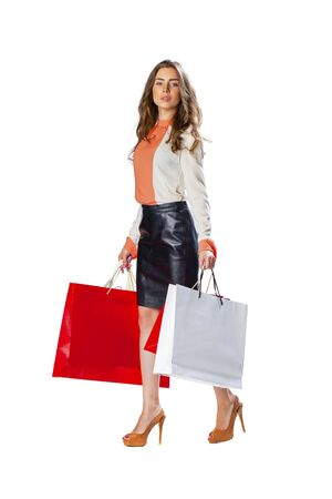 Full length portrait of a beautiful young brunette woman posing with shopping bags, isolated on white background Stock Photo