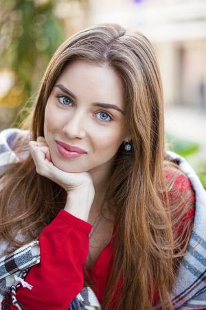 Portret van een mooie jonge vrouw zitten in een cafe op de straat Stockfoto
