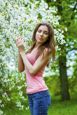bright eyed: Close up portrait of a beautiful young brunette woman on the background of the cherry blossoms, spring park