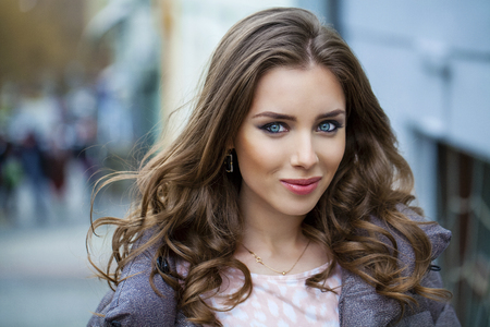 russian: Portrait close up of young beautiful brunette woman, on spring street background