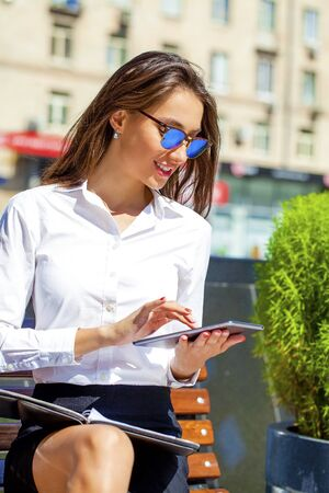 decides: Young beautiful business woman reading notepad