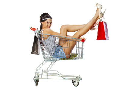 woman shopping cart: Happy young beautiful brunette woman sits in an empty shopping cart with a red bag, isolated on white background