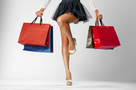 Part body, beautiful female slender legs. Sexy girl holding a paper shopping bags, isolated on white background 免版税图像