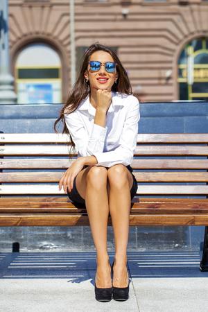 dia soleado: Joven mujer de negocios hermosa que se sienta en un banco en la soleada ciudad