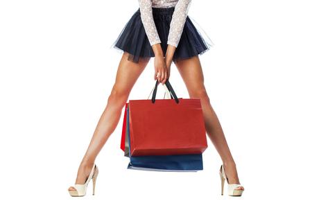 tacones rojos: Parte del cuerpo, hermosas piernas esbeltas mujeres. Muchacha atractiva que sostiene bolsos de compras de papel, aislado en fondo blanco