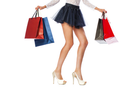 part of body: Part body, beautiful female slender legs. Sexy girl holding a paper shopping bags, isolated on white background Stock Photo