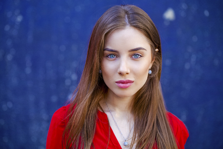 blue face: Sexy young brunette woman, against the background of the dark blue wall