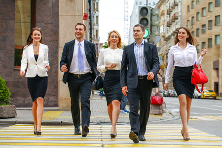 striding: Successful Team of five business people confidently striding along the summer street